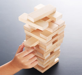hand sliding a wooden block into a tower of blocks